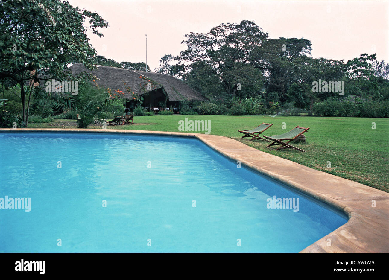 Empty sun loungers beside the pool at the Moivaro Lodge and Coffee Plantation Arusha Tanzania - Stock Image