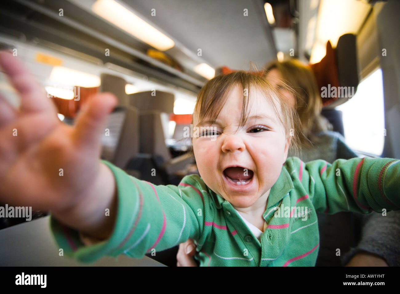 9 month old baby girl sitting on mother's lap and shouting on the eurostar train. Leisure Select class carriage Stock Photo