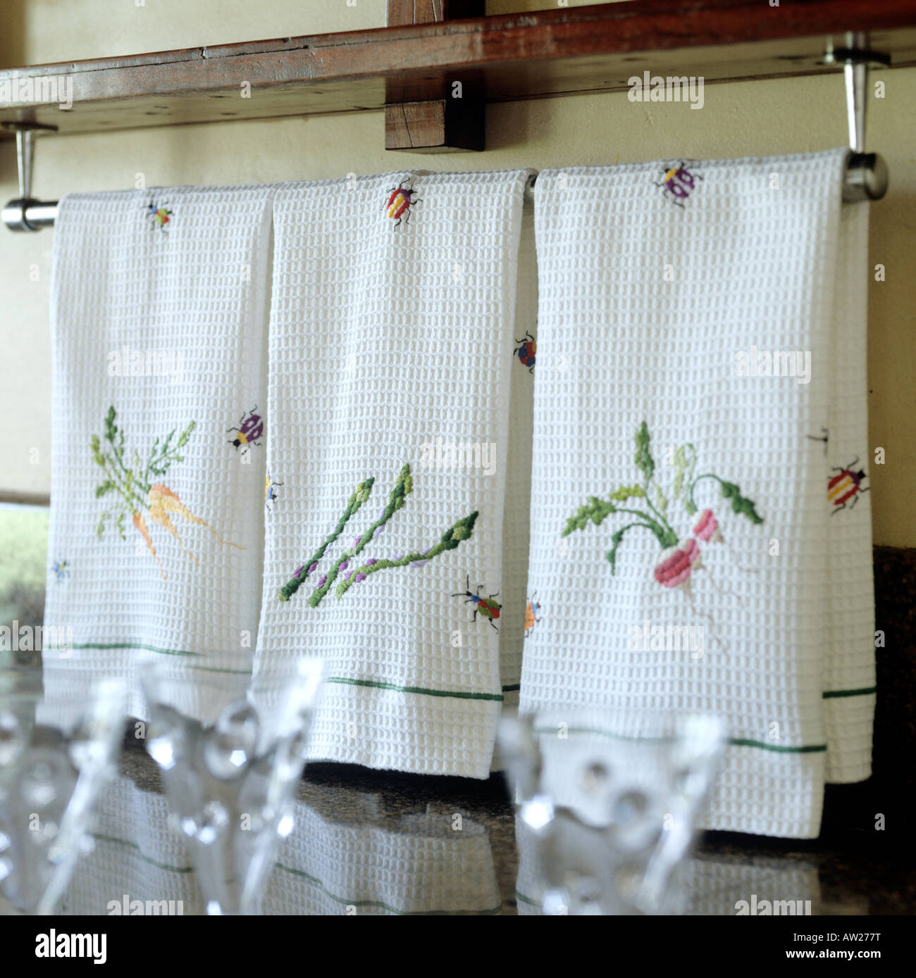 hand embroidered cotton towels arranged on rail in a kitchen Stock ...