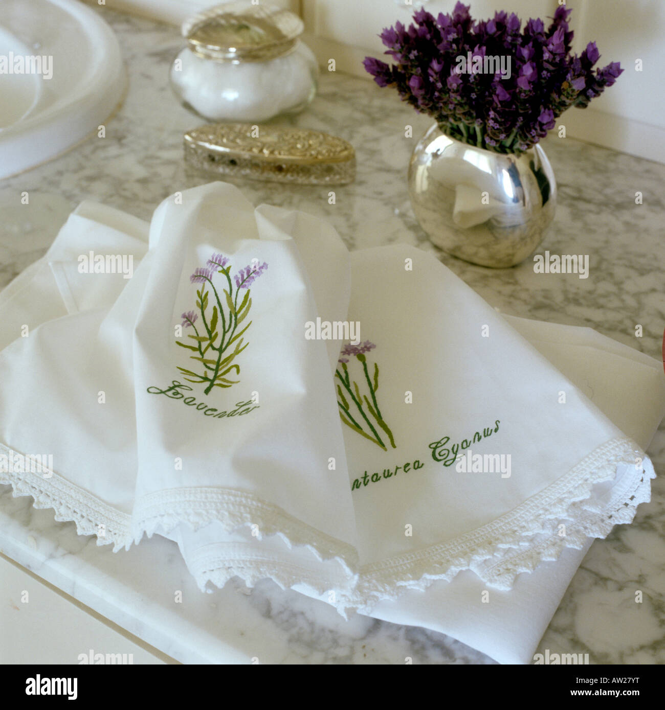 small cotton towels with hand embroidered flower motif on marble surface - Stock Image