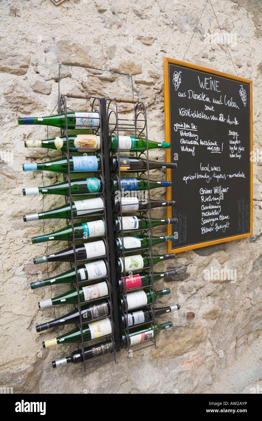 Wine bottles in front of a wall in the wine growing village of Dürnstein in the Wachau region - Stock Image