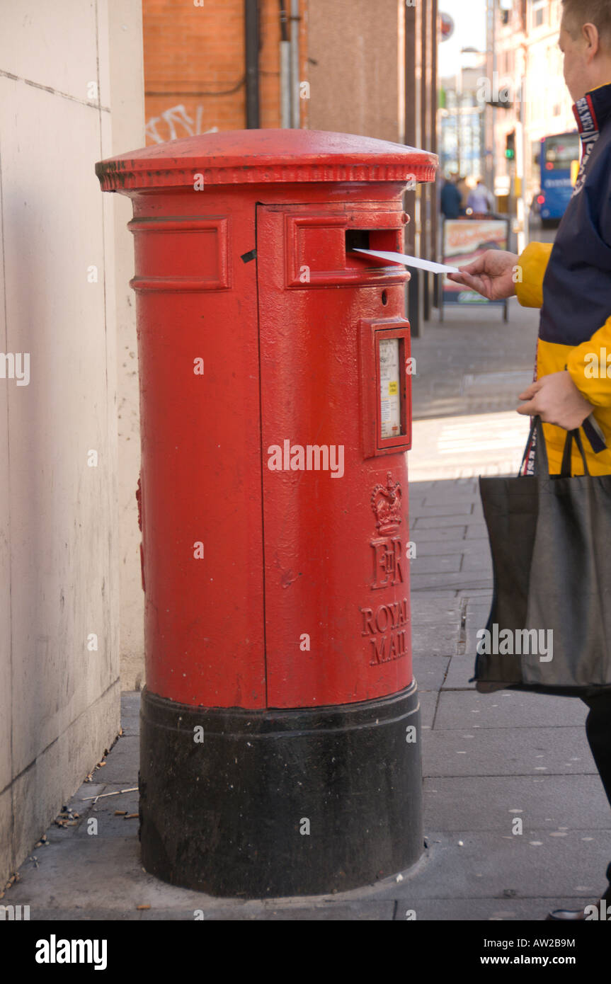 Posting a letter in a red postbox - Stock Image