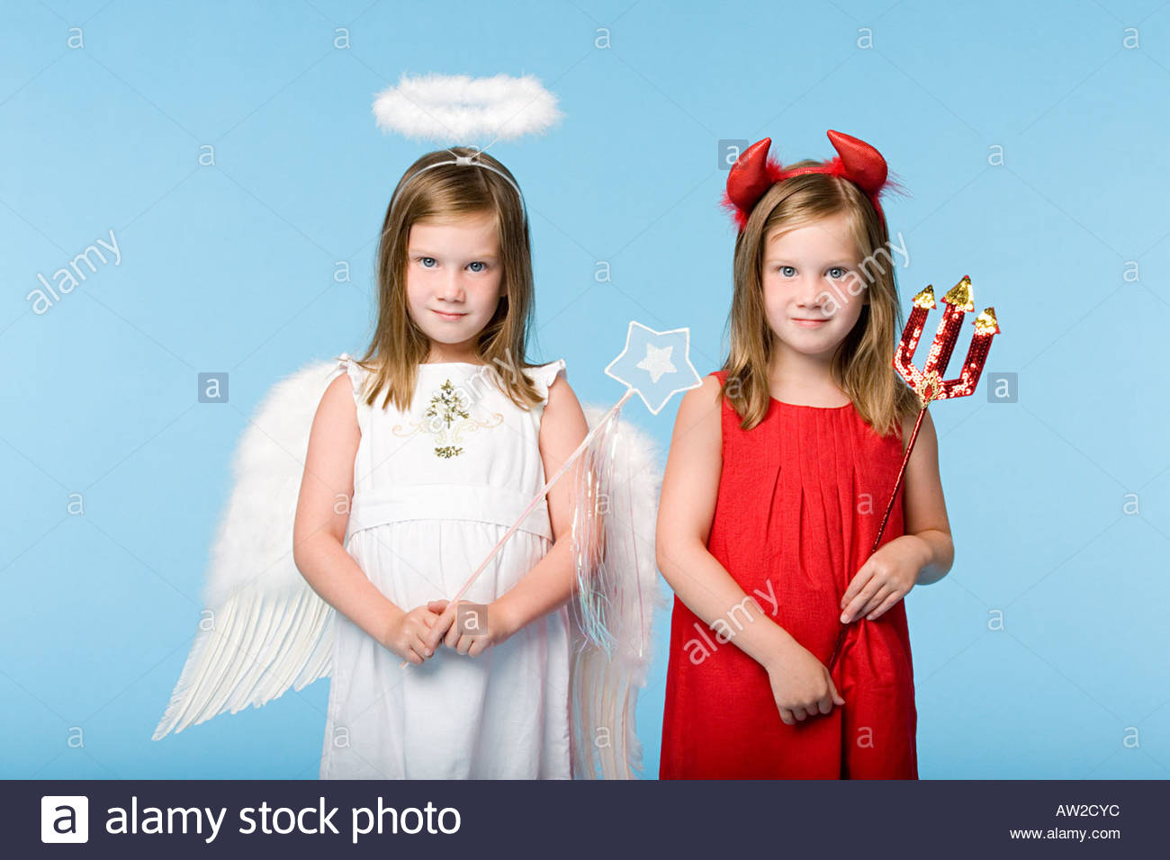 Twin girls dressed as an angel and devil - Stock Image