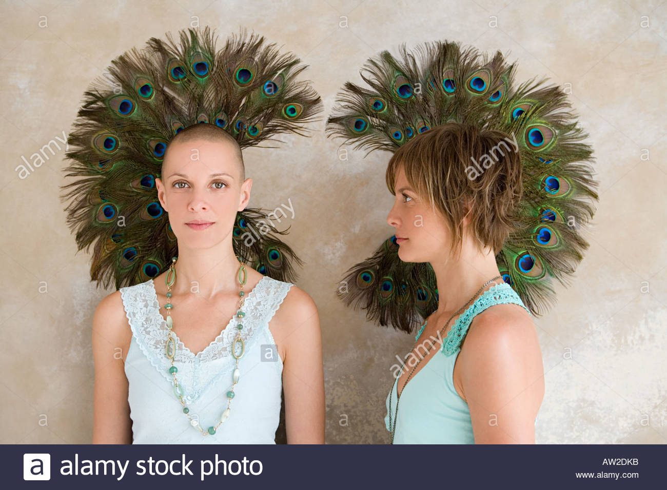 Twin women in front of peacock feathers - Stock Image