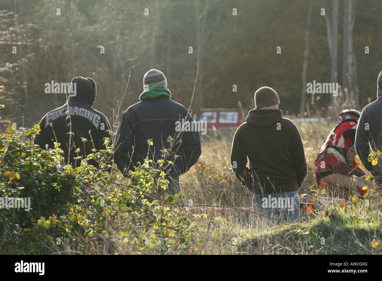 Four young men with their backs to the camera and lit from behind by winter afternoon sunlight watch a motorcycle - Stock Image
