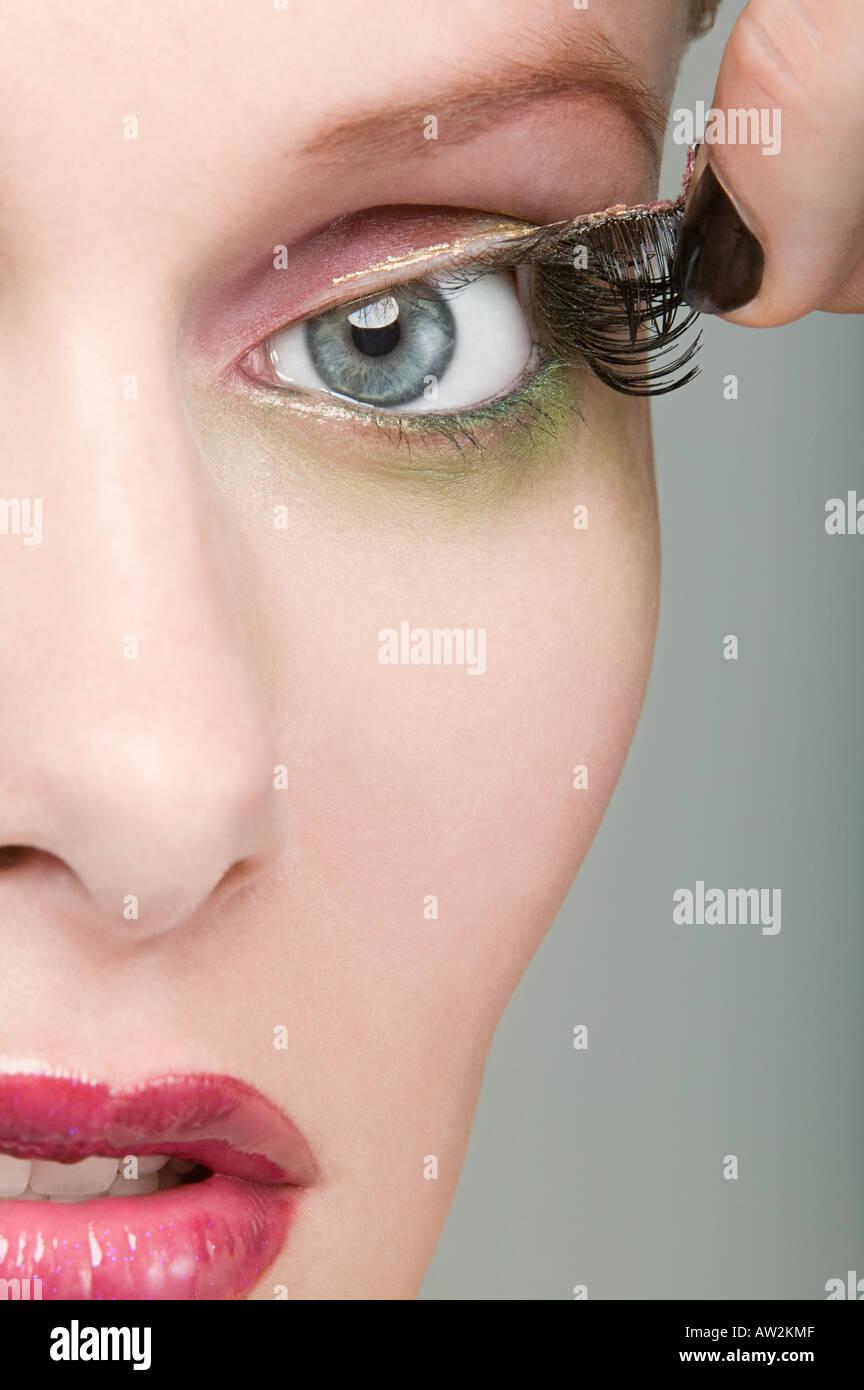 Woman removing fake eyelashes - Stock Image