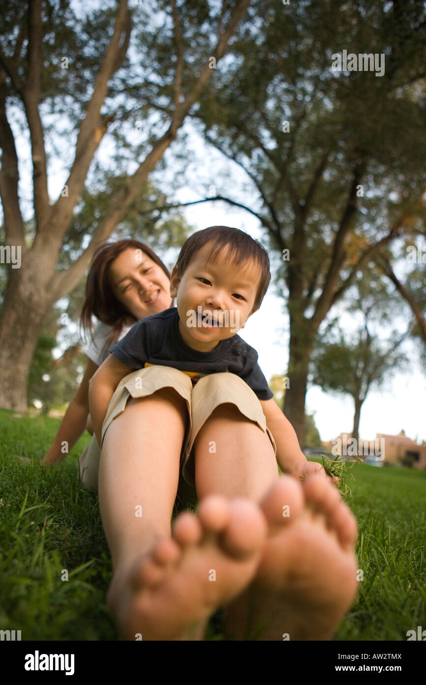 Japanese one year old boy resting on his mother's lap and smiling outdoors at public park - Stock Image