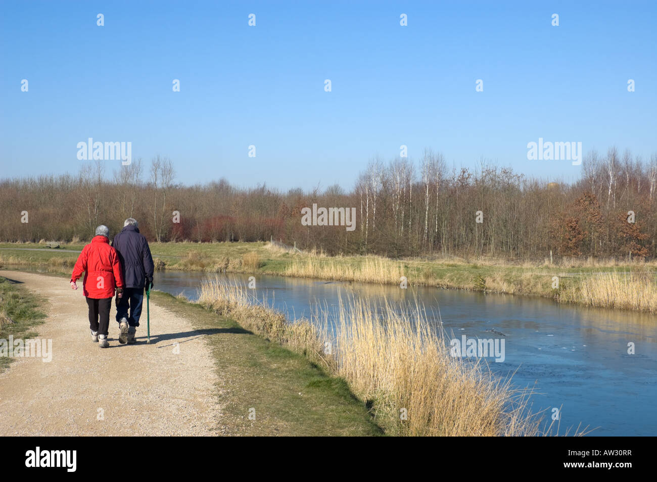 Senior couple walking along a canal towpath Stock Photo