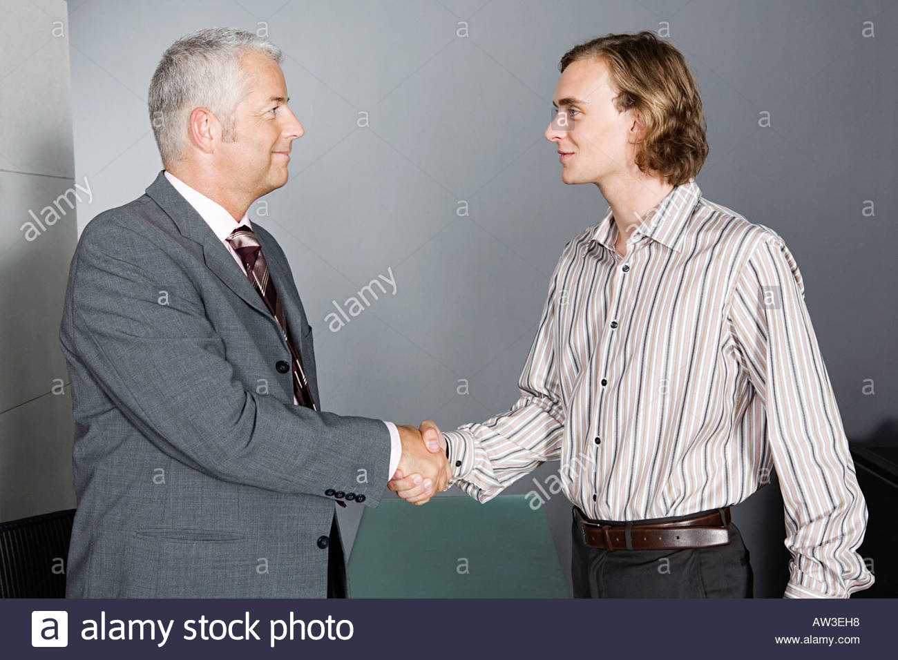 Mature businessman and younger man shake hands - Stock Image