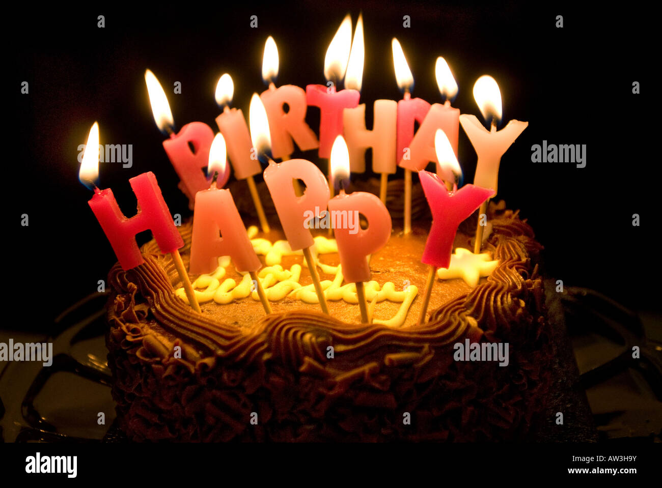 Lighted candles saying Happy Birthday on a chocolate cake Stock