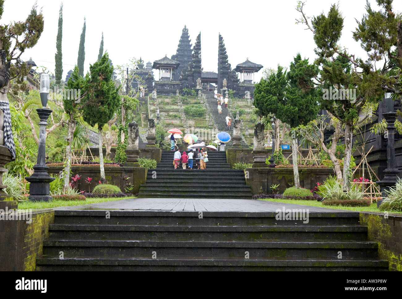 Tourists With Umbrellas Climbing The Steps Into The Pura Besakih Temple Bali Indonesia - Stock Image