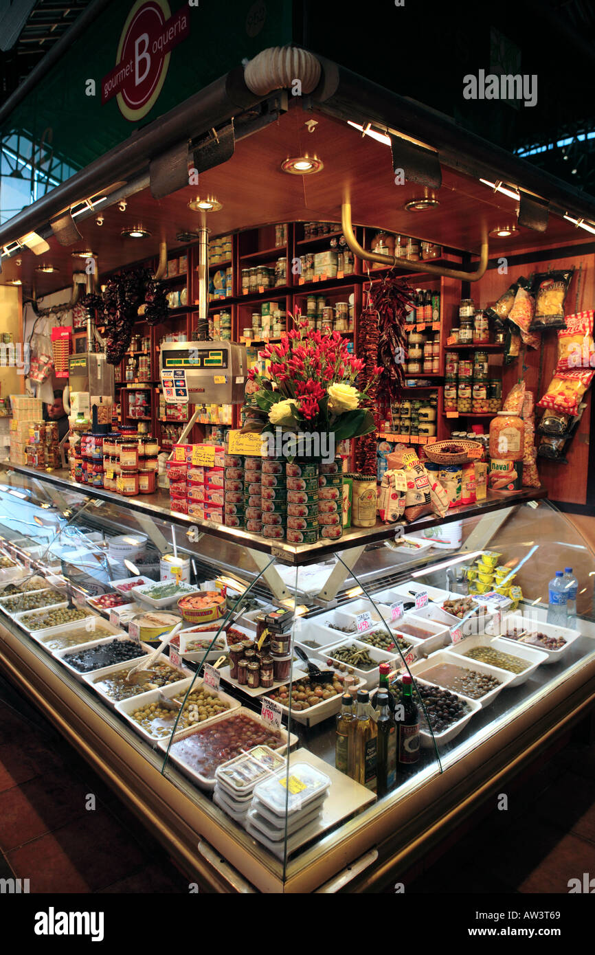 Shop stall in the Boqueria selling olives, various condiments and tinned fish products - Stock Image