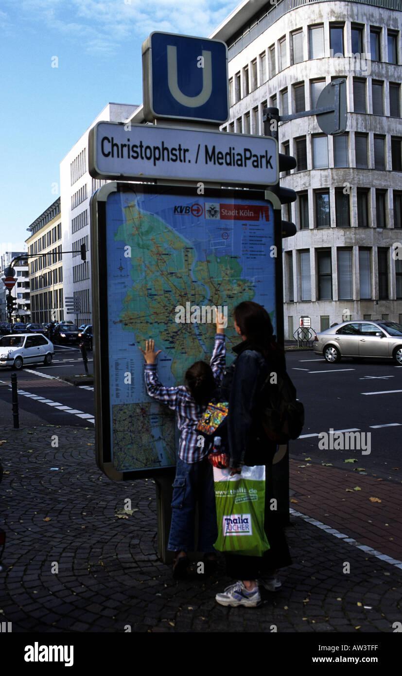 People looking at a street plan outside Christoph Street / Media Park U-Bahn in Cologne, North Rhine-Westphalia, Stock Photo