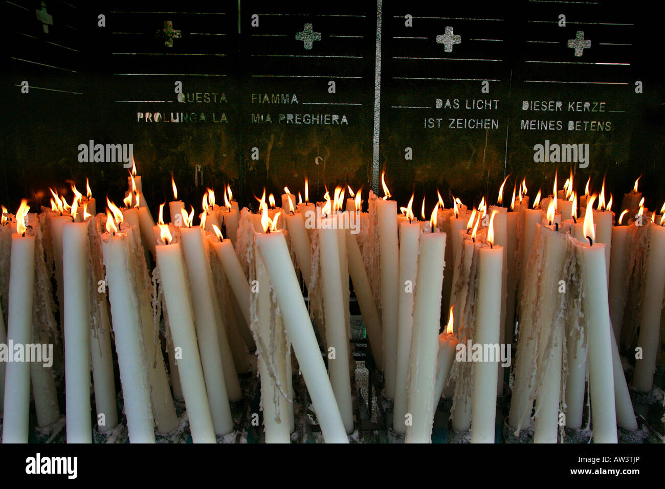 Candles burning to remember loved ones at Lourdes in France. - Stock Image