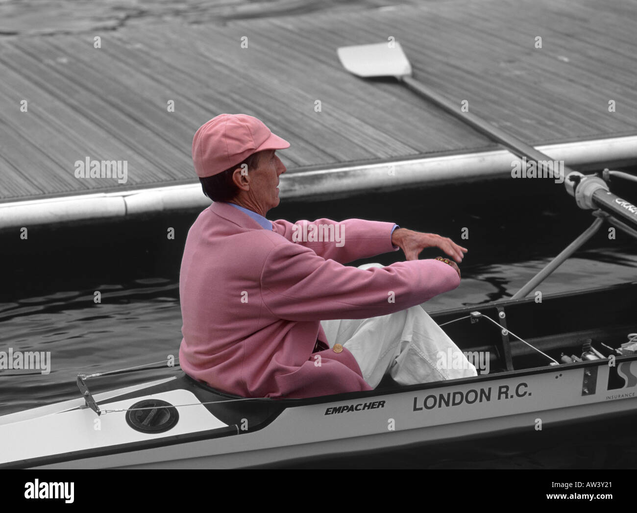 Mono and pink manipulated image: Cox of the Leander Club sitting in stern of rowing boat at Henley Royal Regatta, Stock Photo