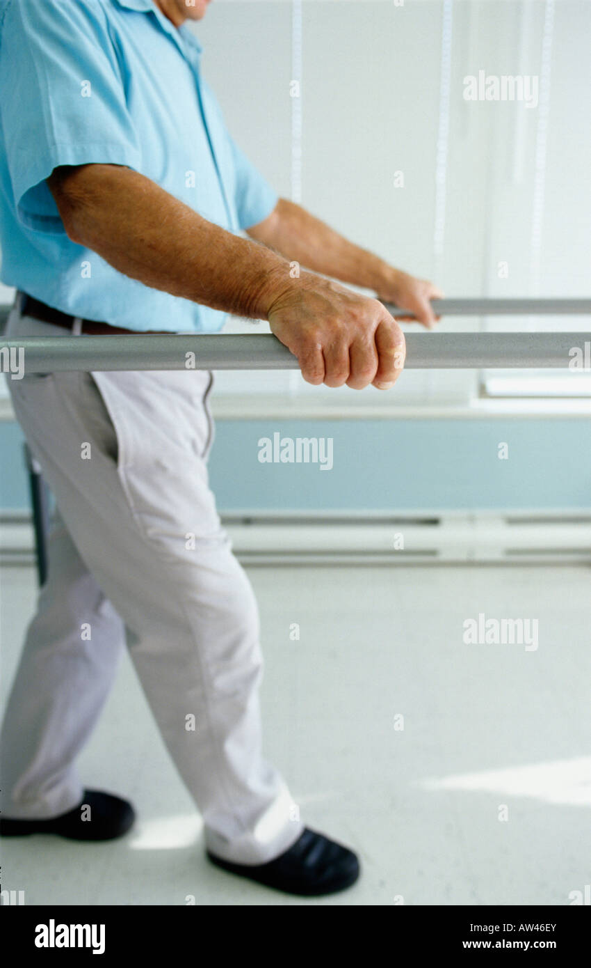 Patient using the walking parallel bars as rehabilitation - Stock Image