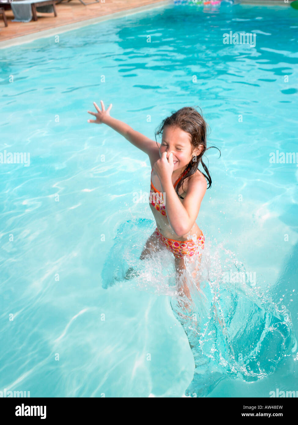 Girl jumping in swimming pool. Stock Photo