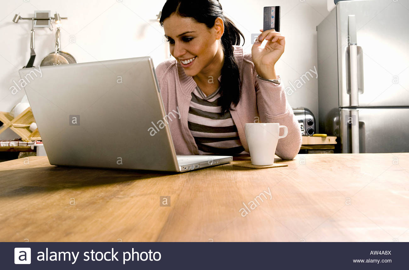Woman looking at laptop with credit card. - Stock Image