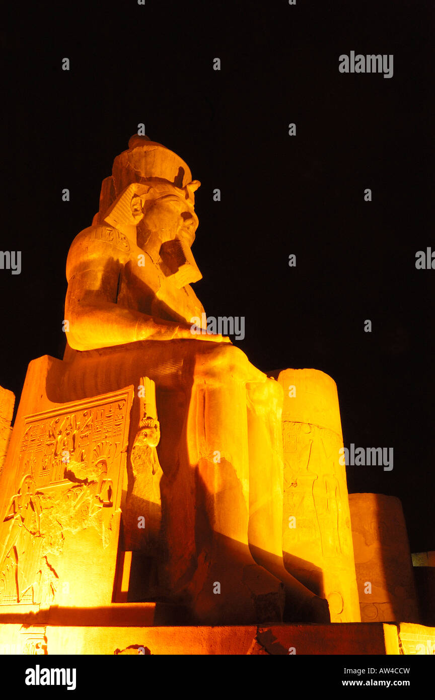 Colossal statue of Rameses II on his throne in the Temple of Luxor, lit by flood light  in Luxor, Egypt - Stock Image