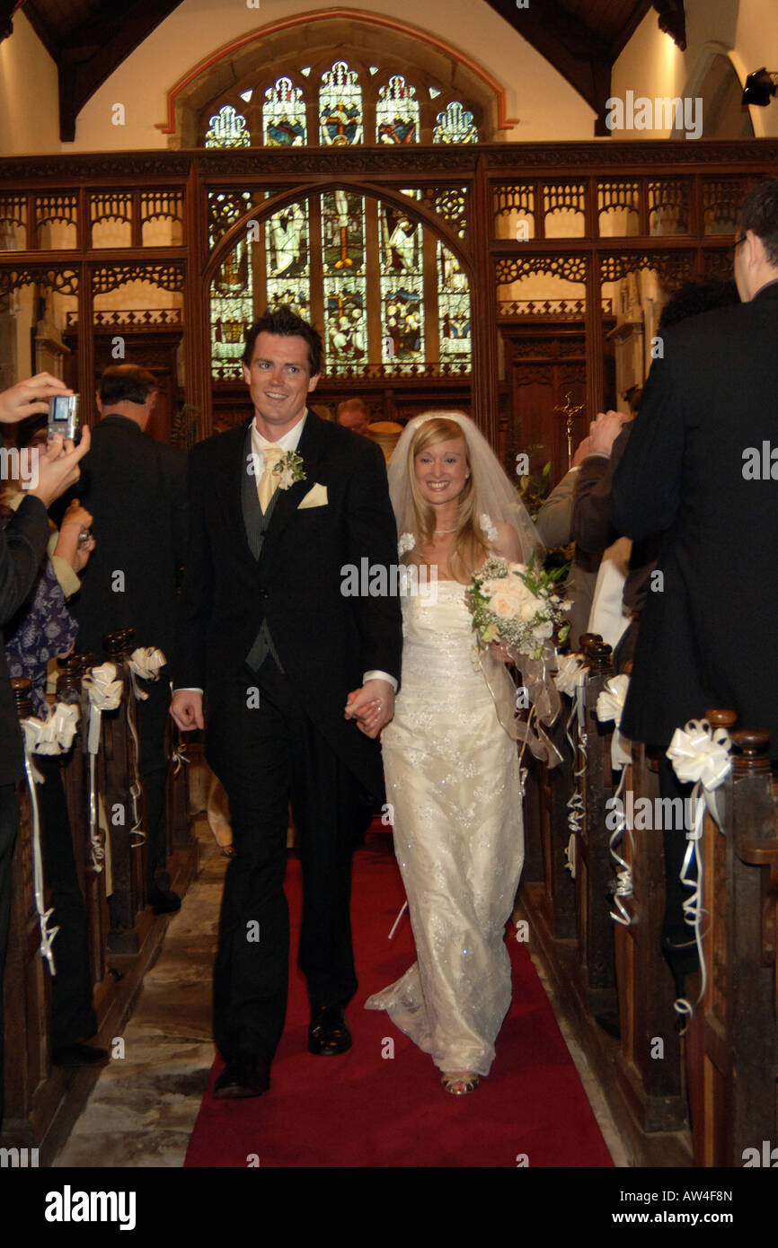 A couple walk down the church aisle after getting married Model Released - Stock Image