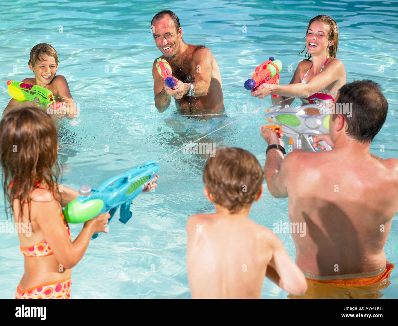 Kids and adults playing with water guns. - Stock Image