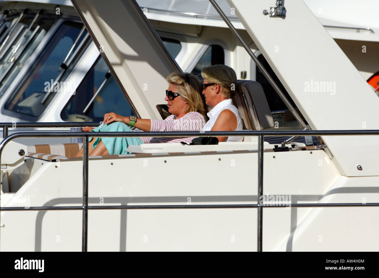 a woman and man lady and gentleman sat on a luxury motor yacht in the sunshine wearing sunglasses and relaxing during - Stock Image