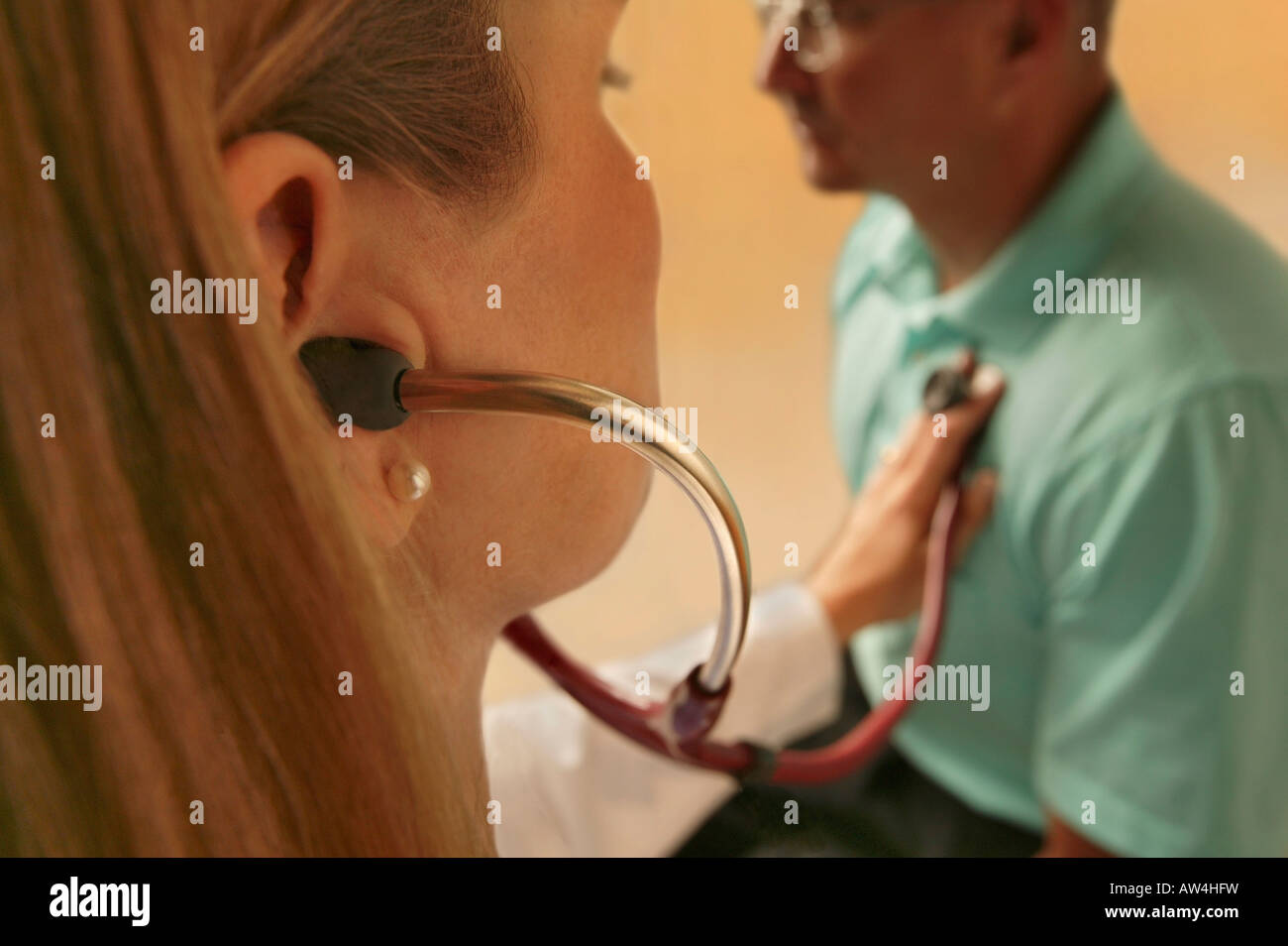 A female doctor uses a stethoscope to listen to a male patients heart. - Stock Image