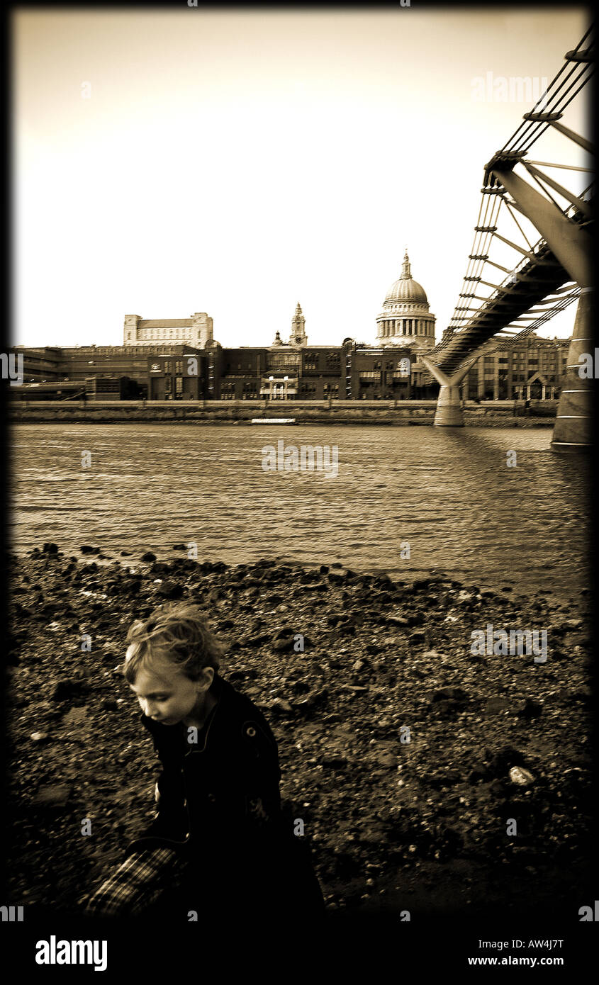 sepia london scene of young boy on bankside with millennium bridge and st pauls in the background - Stock Image