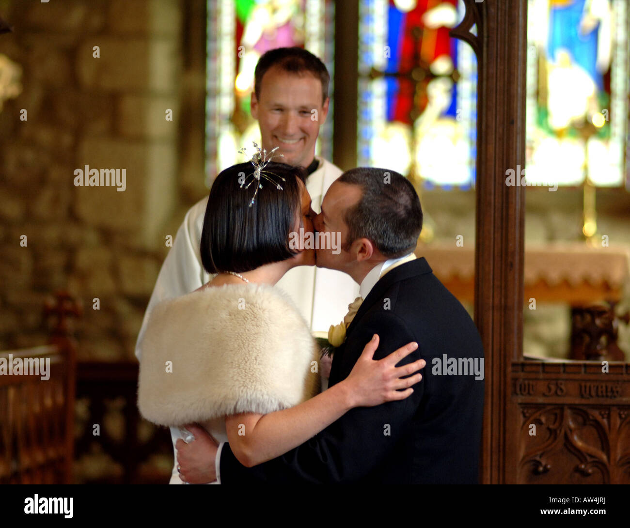 A couple kiss at the church aisle after getting married Model Released - Stock Image