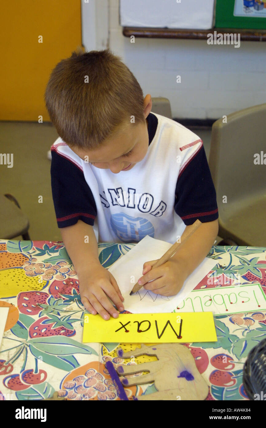 Boy in nursery  class learning how write his name - Stock Image