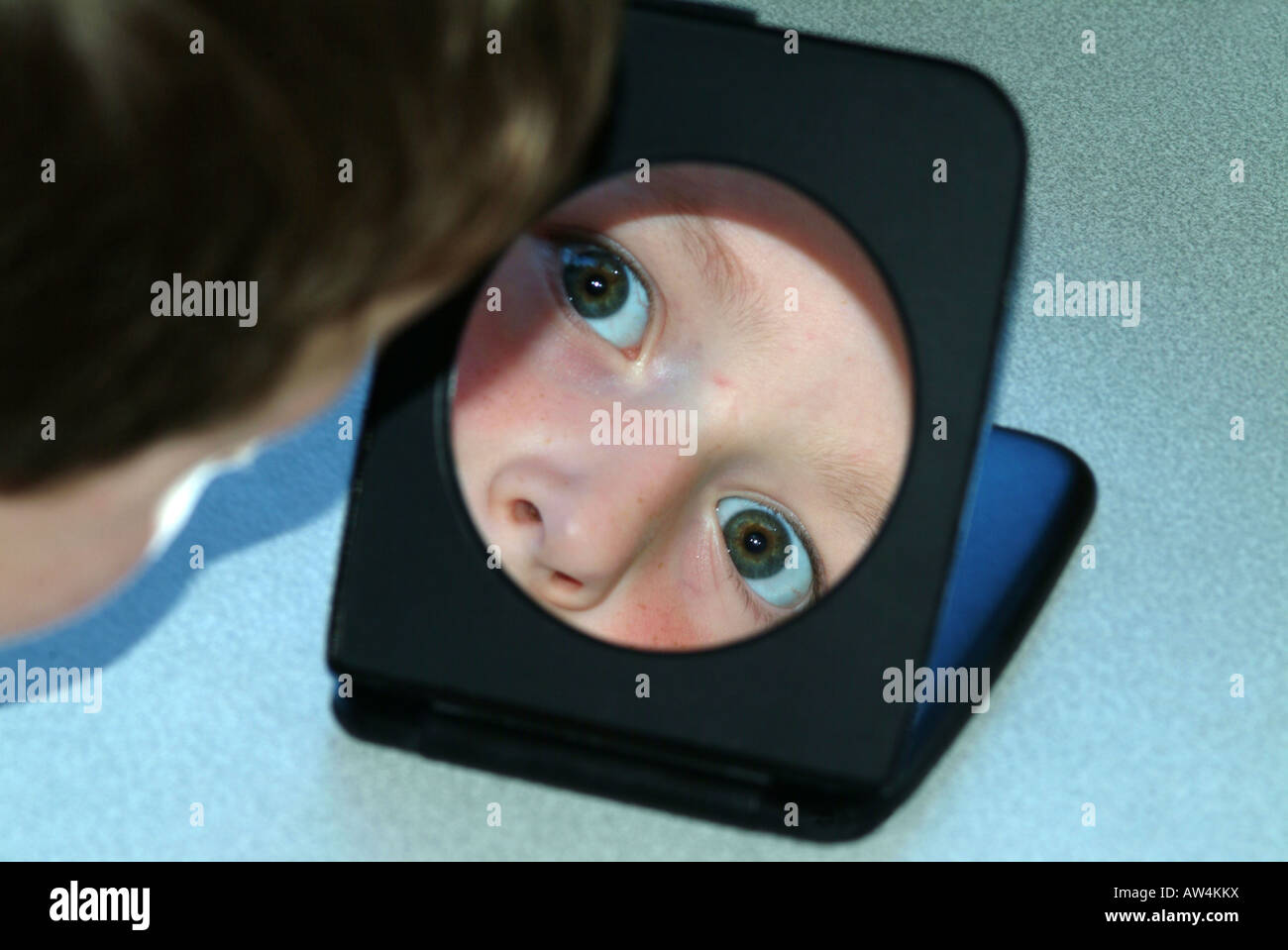 boy reflected in shaving mirror - Stock Image