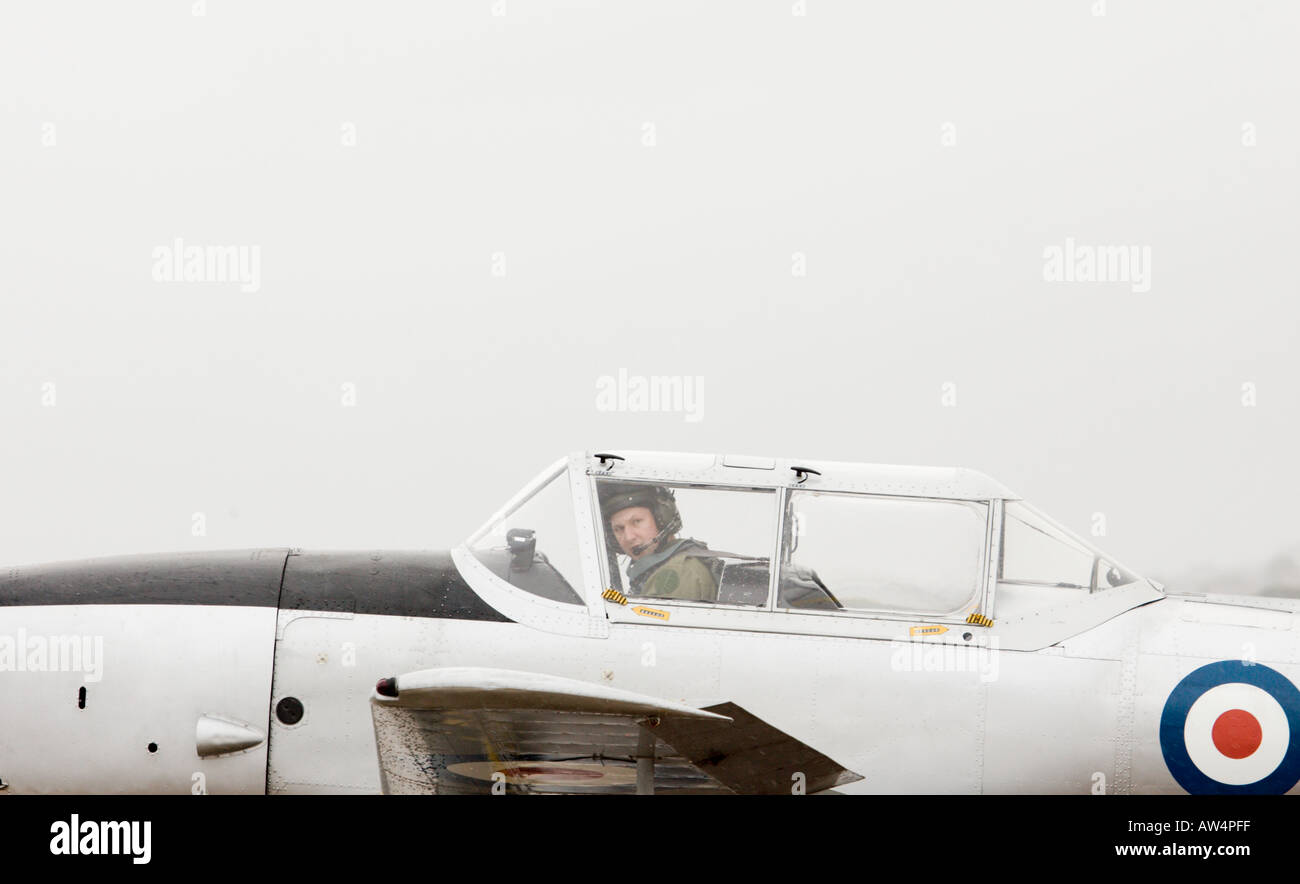 Pilot peering from the cockpit of a Hurricane WWII WW2 fighter plane - Stock Image