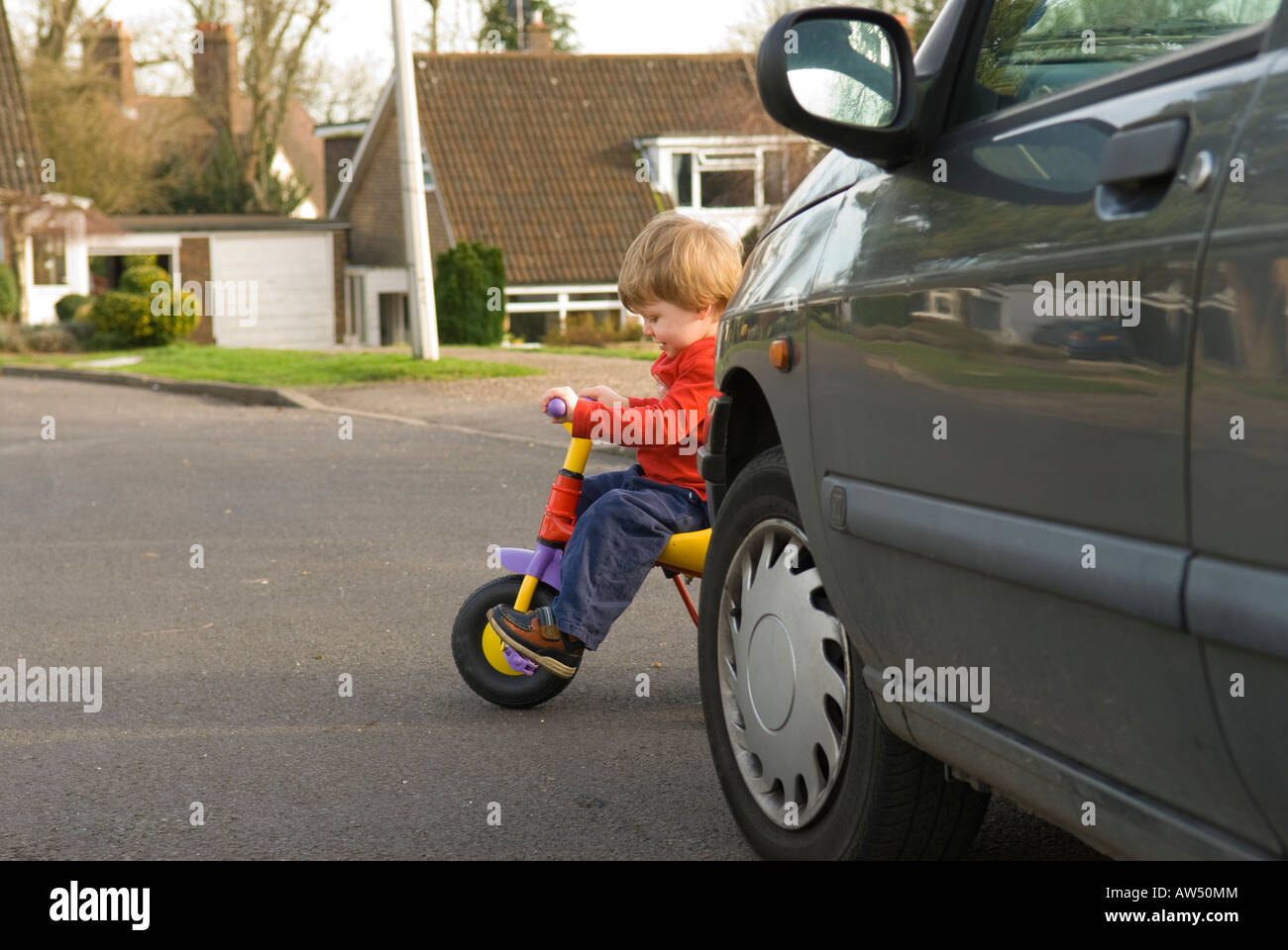 two year old boy on bike in danger on road pulling out from behind a