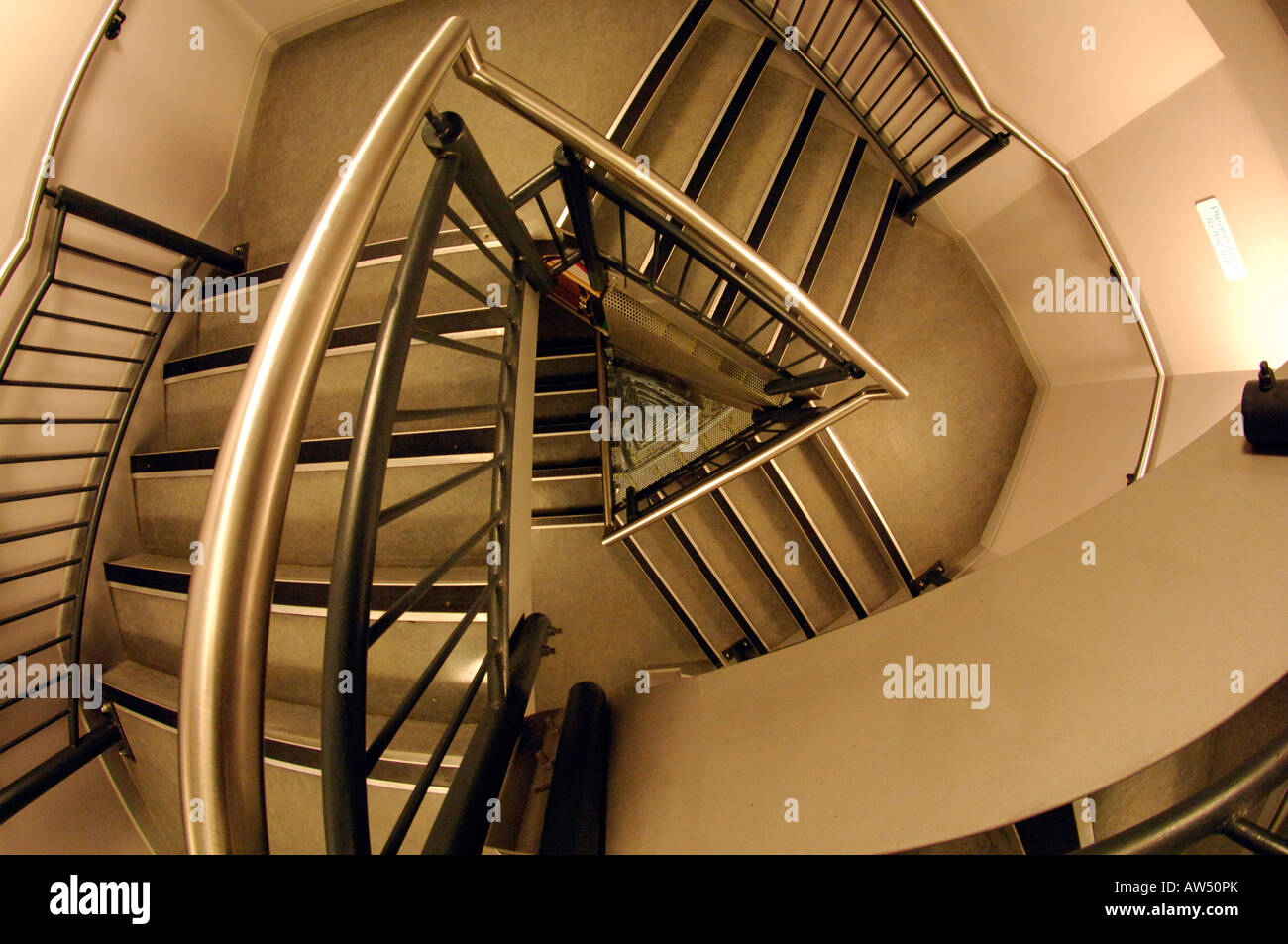 a modern staircase stairwell well spiraling looking down through the steps stairs through multiple floors towards Stock Photo