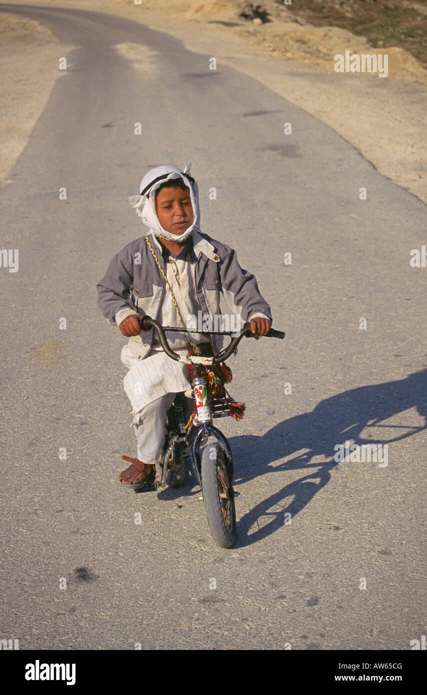 A young Palestinian boy on an old bicycle near the city of Jericho Stock Photo