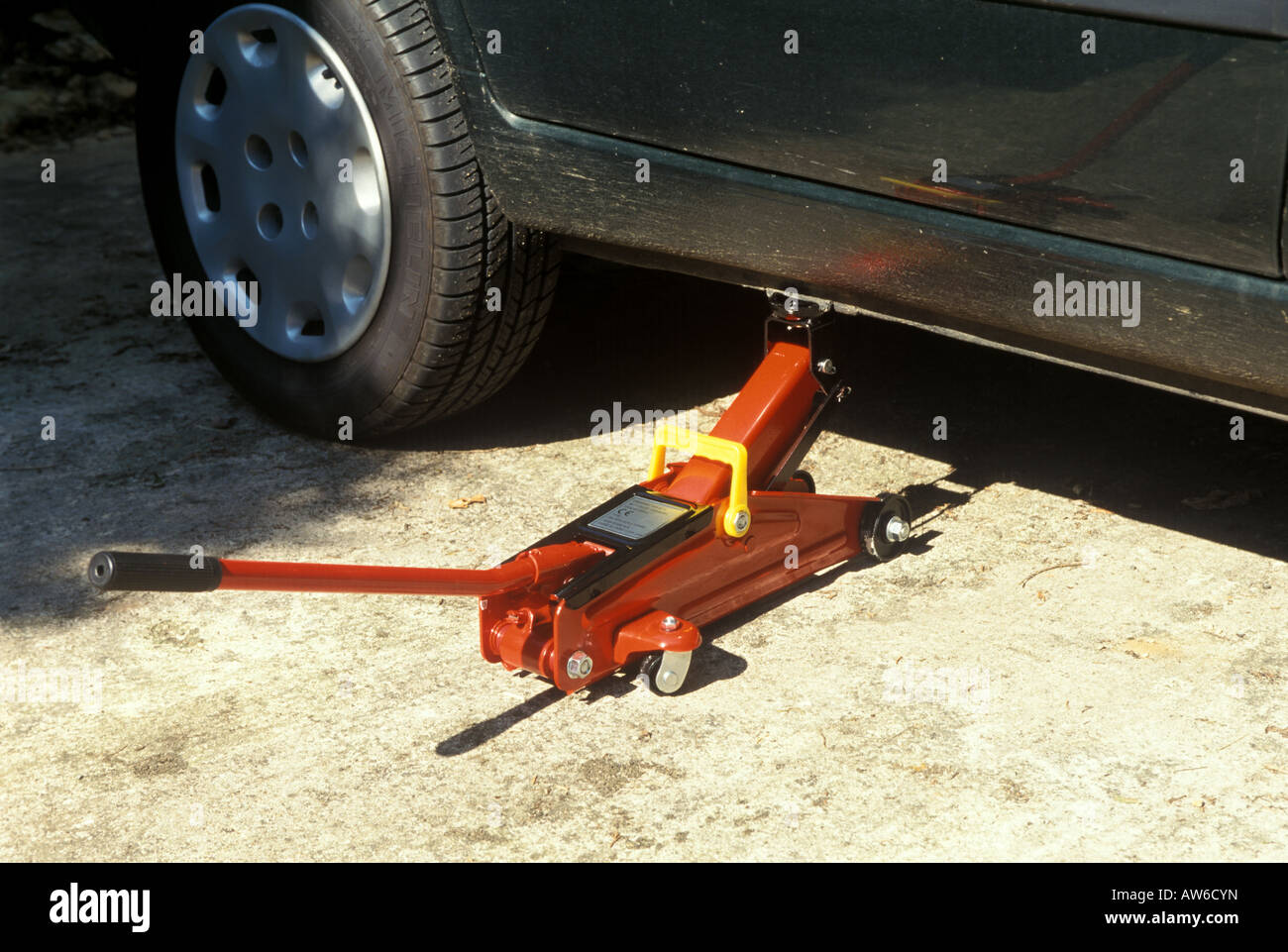 A motorist hydraulic car jack being used to raise a car - Stock Image