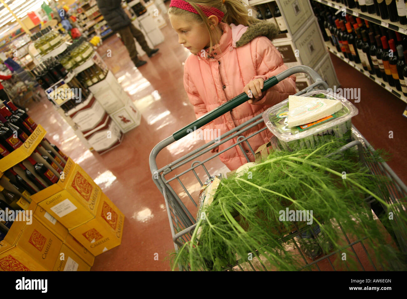 Girl shopping in grocery store buying produce - Stock Image