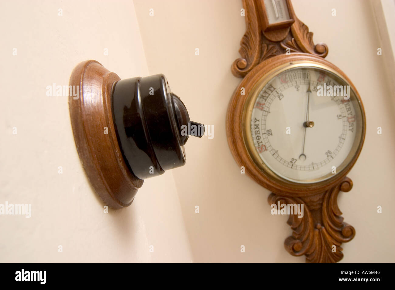 OLD FASHIONED BAKELITE LIGHT SWITCH WITH BAROMETER IN BACKGROUND - Stock Image