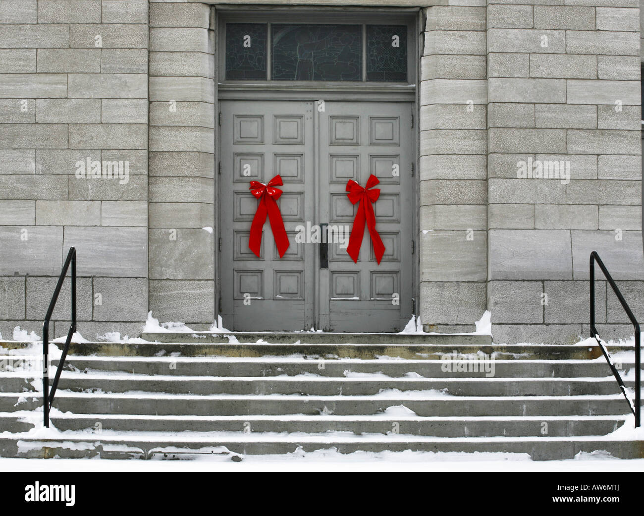 Red bows on doors of a grey building - Stock Image