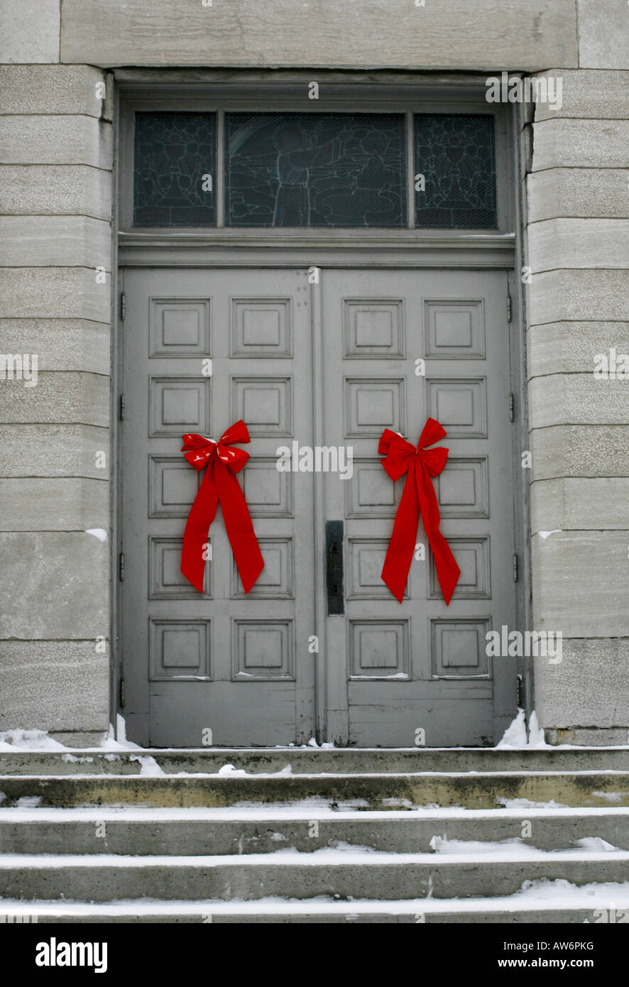 Red bows on doors of a grey building, Waterloo, Quebec - Stock Image