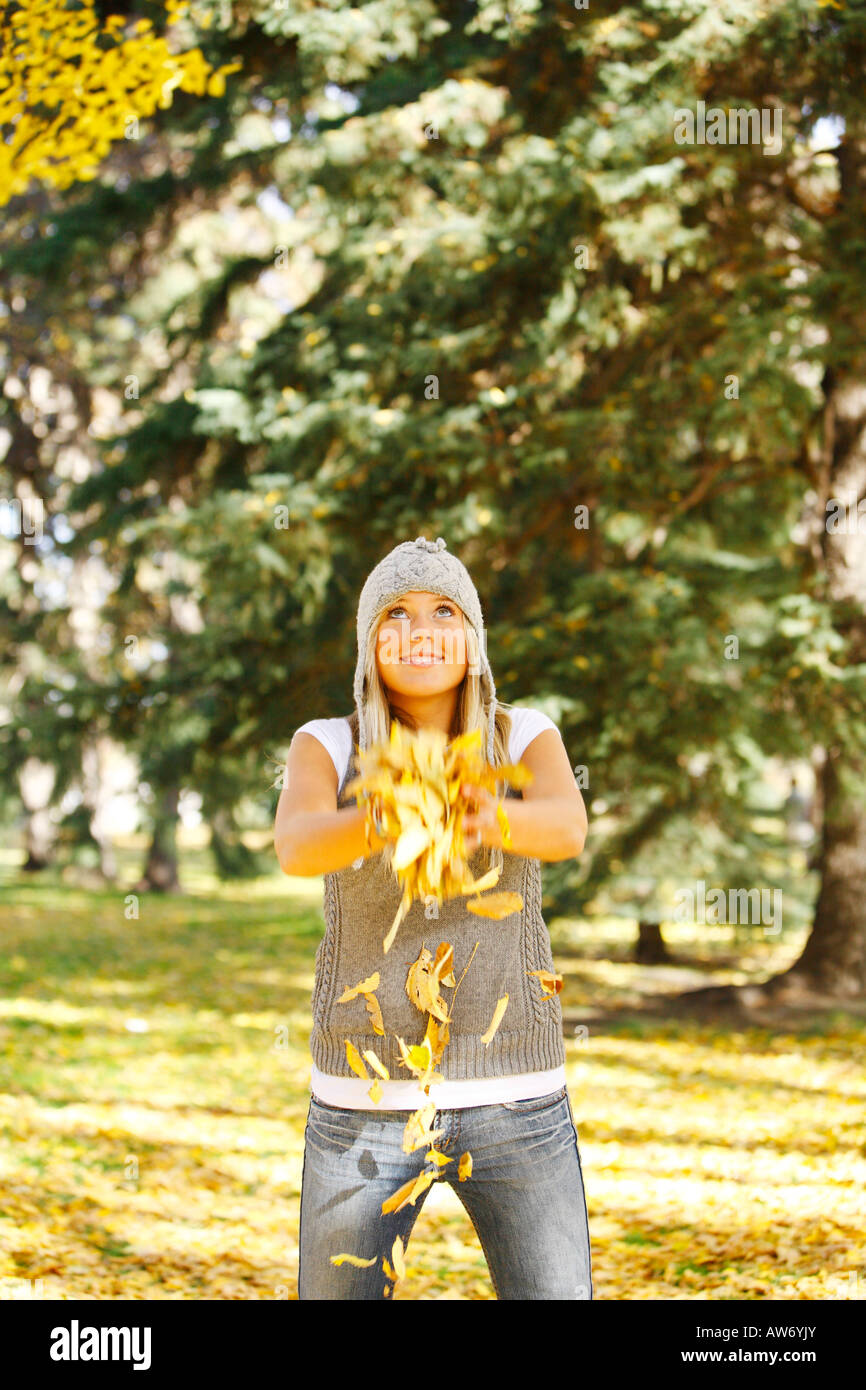 A teenage girl throwing leaves - Stock Image