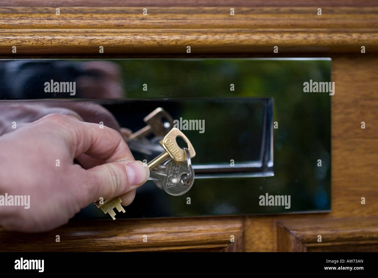 posting keys through the letterbox of a house due to inability to pay mortgage - Stock Image