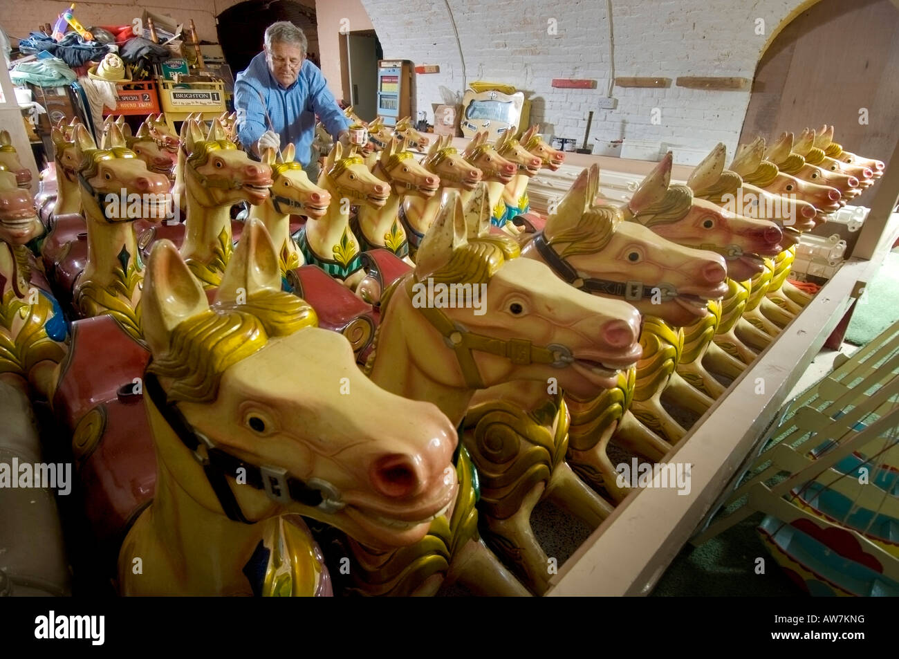 Fairground carousel horses in storage having winter repairs done out of season. - Stock Image