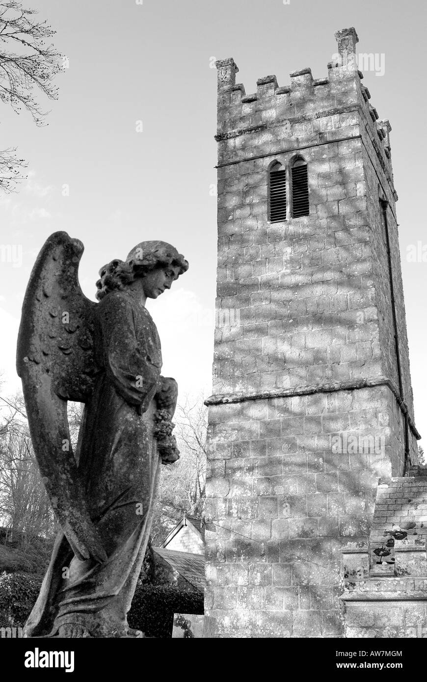 The tower of Holy Trinity church at Gidleigh on Dartmoor with a stone angel in the foreground in monochrome - Stock Image
