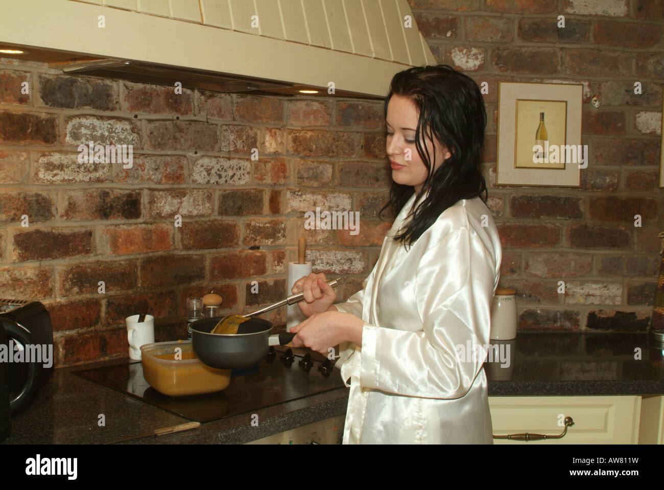 97df91e021 A girl in her twenties a white satin robe making breakfast in a farmhouse  kitchen