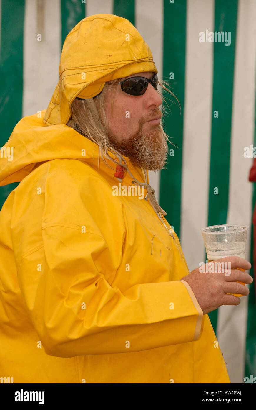 a hairy bker rocker dressed in yellow oil skins mutton dressed as lamb a wolf in sheeps clothing wearing sunglasses - Stock Image