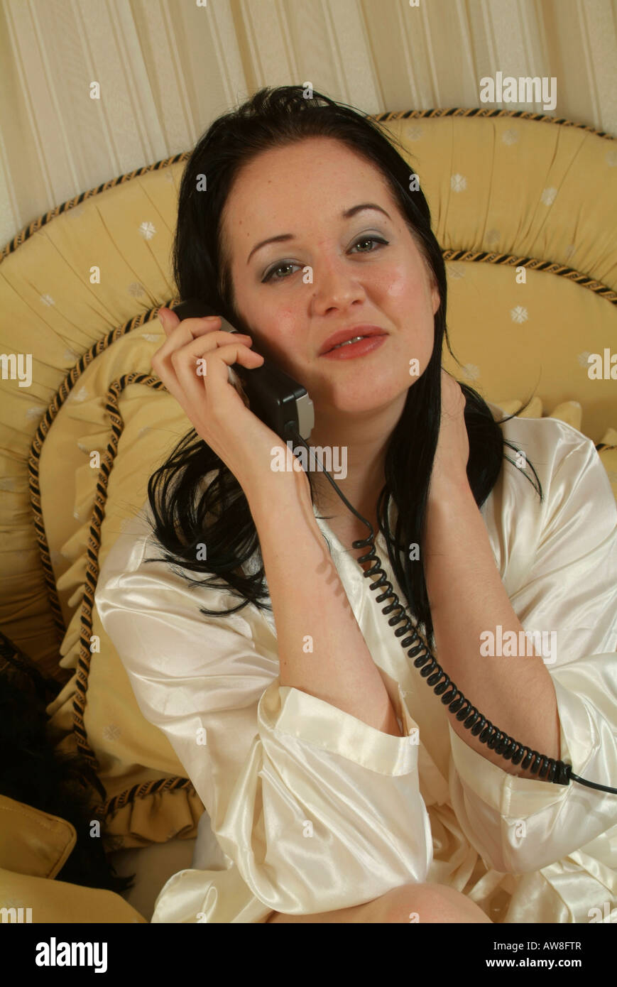 64291cd184 A girl in her twenties sitting in bed wearing a white satin robe talking on  the
