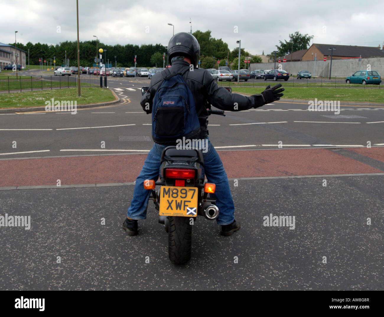 A motorcyclist signalling to turn right - Stock Image