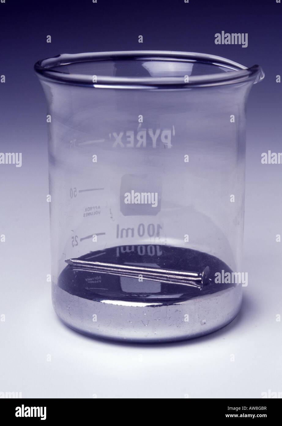 An iron nail floating on mercury - Stock Image