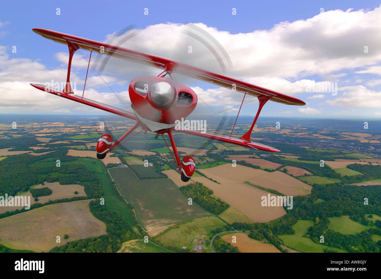 A red stunt biplane in flight over rural countryside - Stock Image